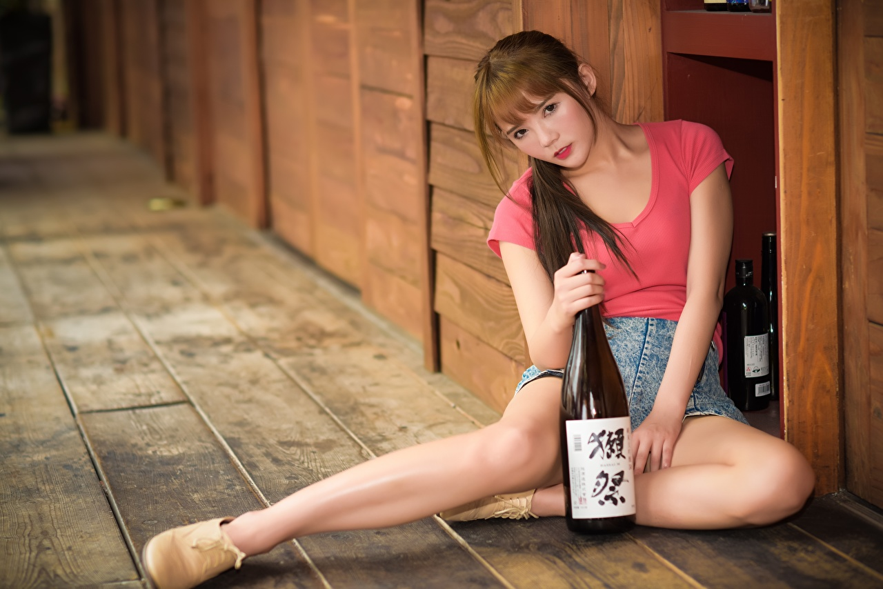 Image Brown haired Bokeh female Legs Asian Hands Bottle Sitting blurred background Girls young woman Asiatic sit bottles