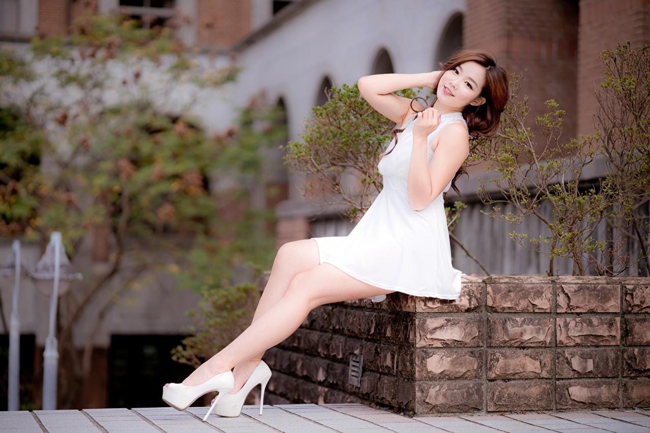 Bilder Braune Haare unscharfer Hintergrund Mädchens Bein Asiatische Hand sitzt Kleid High Heels Braunhaarige Bokeh junge frau junge Frauen Asiaten asiatisches sitzen Sitzend Stöckelschuh
