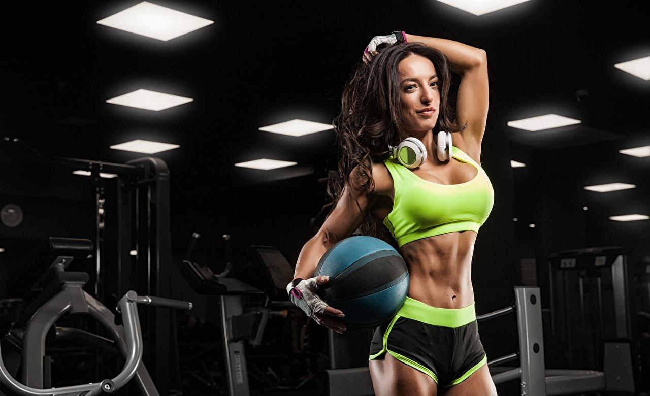 Fotos Brünette Kopfhörer Handschuh posiert Fitness Sport junge frau Hand Ball Bauch Shorts Pose Mädchens sportliches junge Frauen
