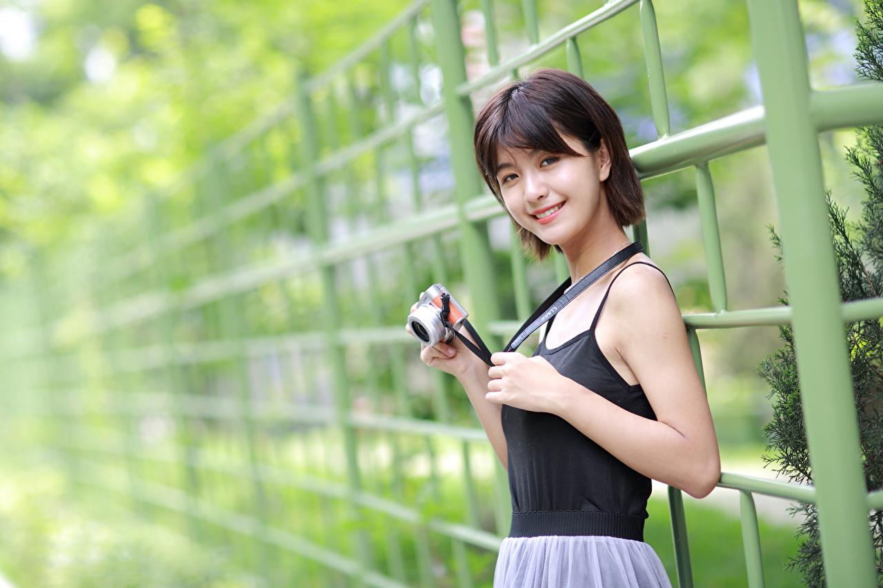 Achtergrond Fotocamera Glimlach Jonge vrouwen Aziaten Kijkt fototoestel jonge vrouw aziatisch