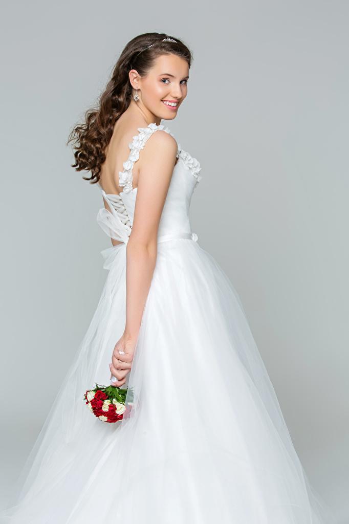 Hintergrundbilder Braut Braune Haare Lächeln Mädchens Grauer Hintergrund Kleid bräute Braunhaarige