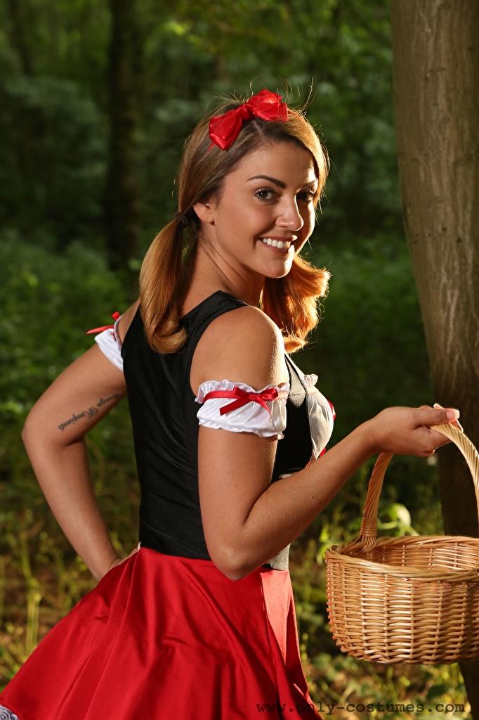 Bilder junge frau Bryoni-Kate Williams Braune Haare Lächeln Rotkäppchen Weidenkorb Hand Uniform Schleife Starren  für Handy Mädchens junge Frauen Braunhaarige Blick