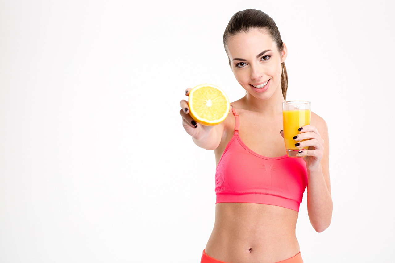 Pictures Smile Healthy eating Girls Juice Orange fruit Highball glass Food Staring White background female young woman Glance
