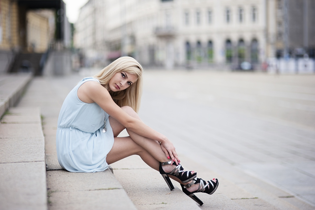Photos Blonde girl Bokeh female Stairs Legs sit Hands frock Stilettos blurred background Girls stairway staircase young woman Sitting gown Dress high heels