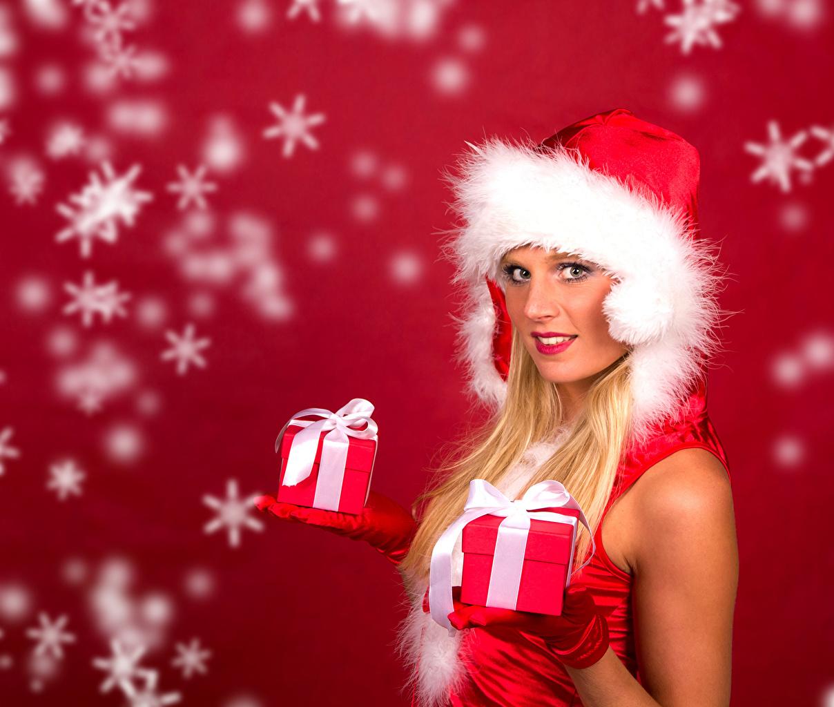 Bilder Neujahr Blond Mädchen Mütze junge Frauen Schneeflocken Geschenke Roter Hintergrund Blondine Mädchens junge frau