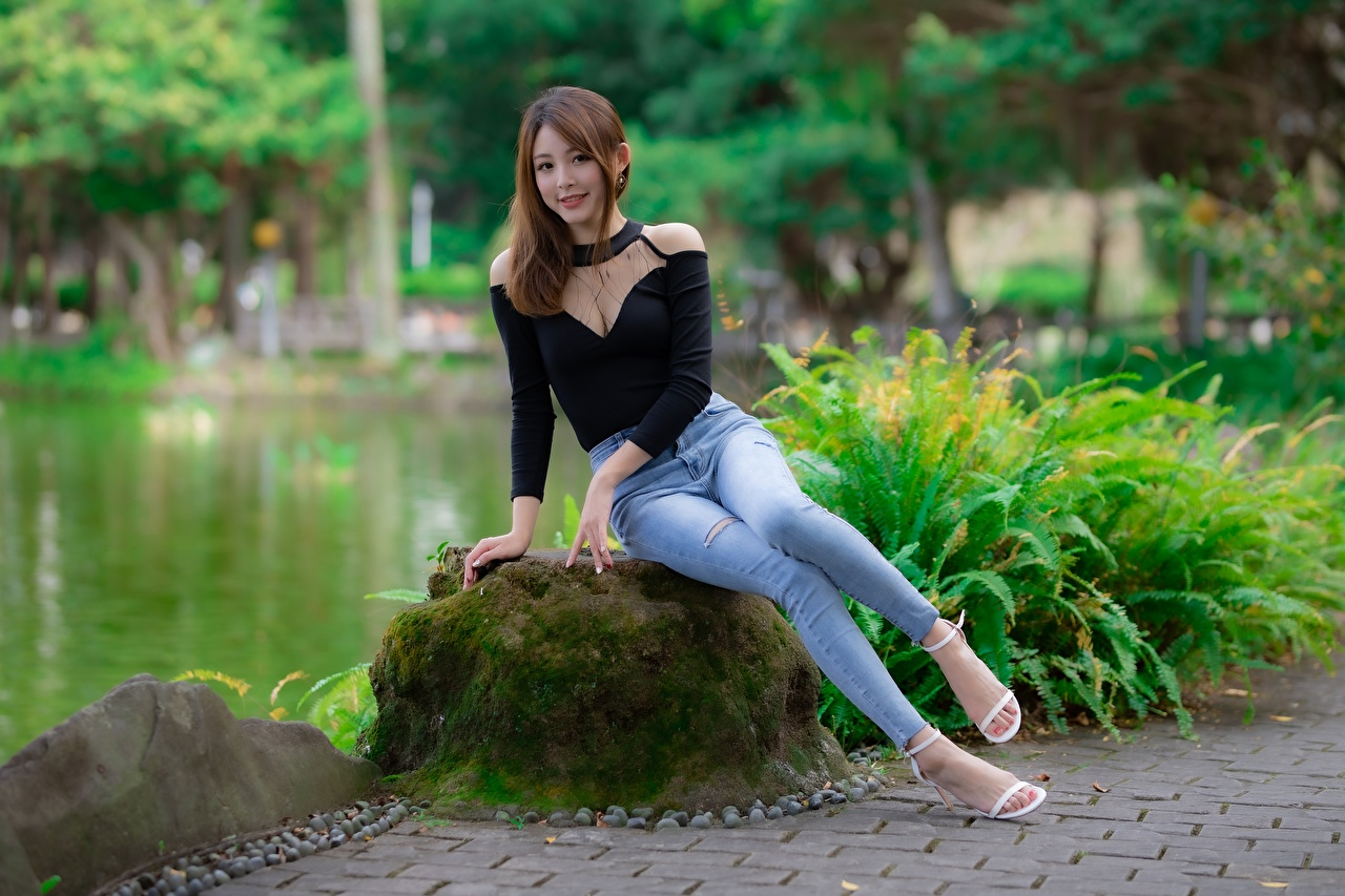 Images Brown haired female Legs Jeans Asiatic sit Moss stone Hands Shrubs high heels Girls young woman Asian Stones Sitting Bush Stilettos