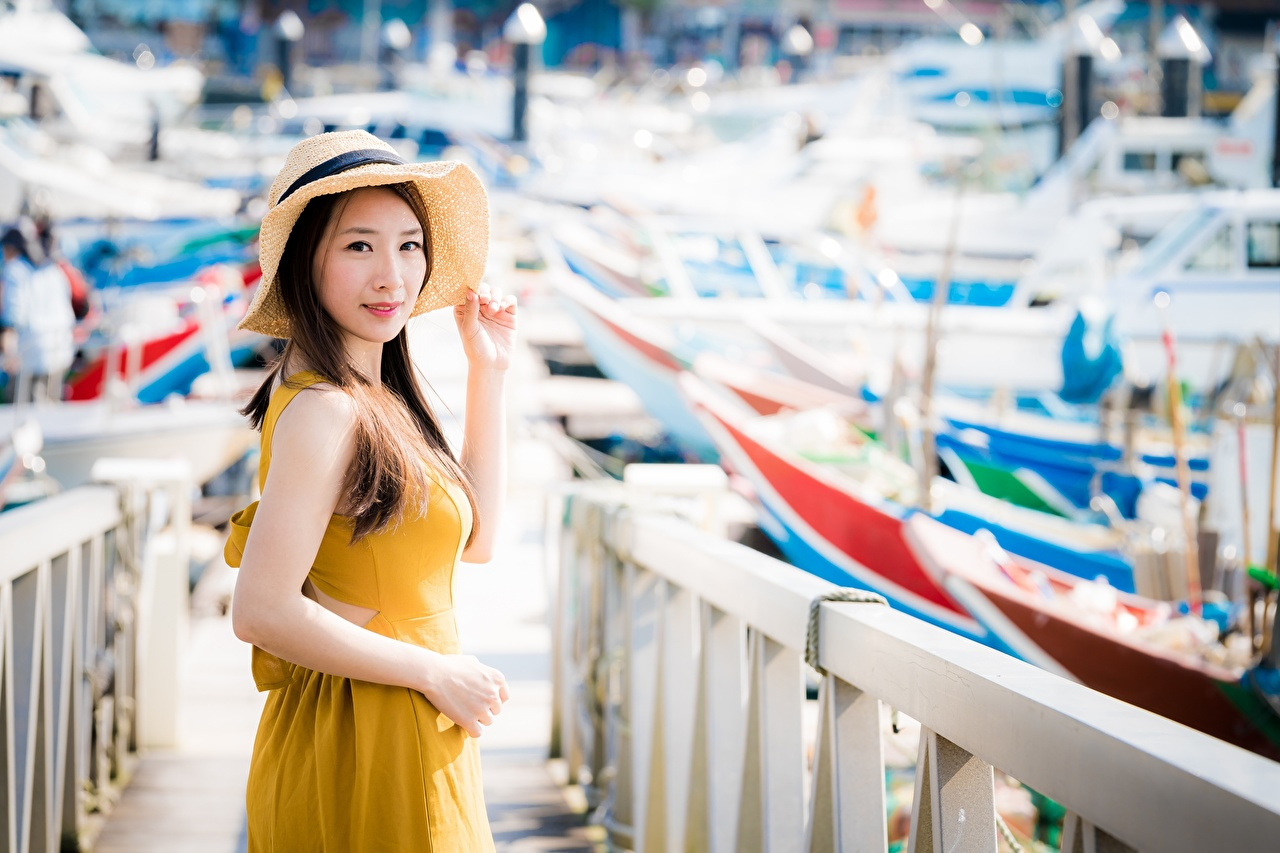 Images Brown haired blurred background Hat Girls Fence Asian Hands Glance Bokeh female young woman Asiatic Staring