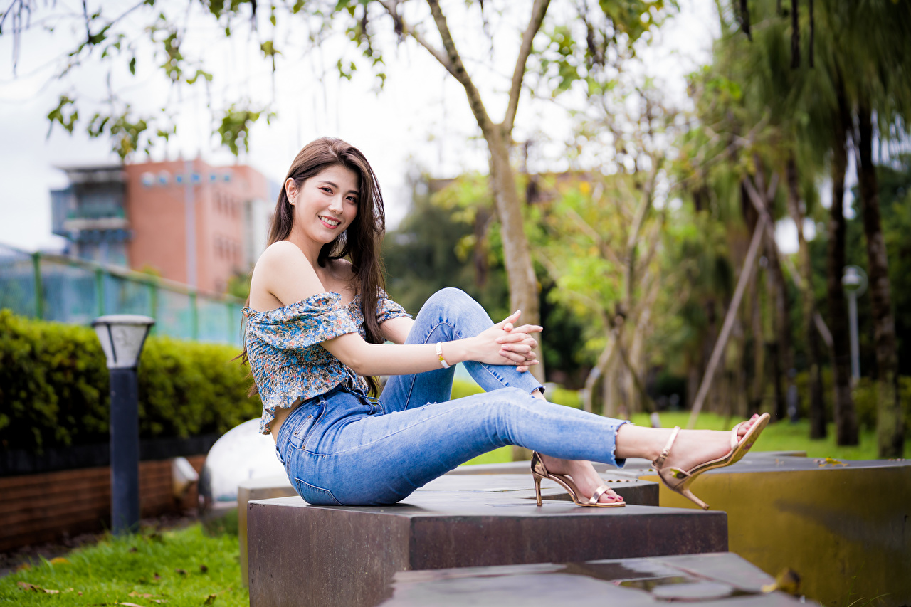 Image Smile young woman Legs Jeans Asiatic Sitting Glance Girls female Asian sit Staring