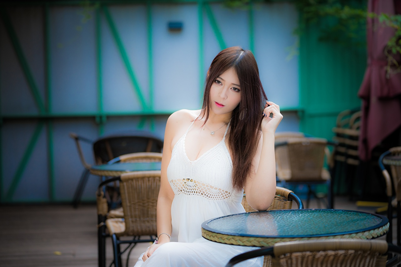 Desktop Wallpapers Brown haired blurred background Girls Asian sit Hands Staring Dress Bokeh female young woman Asiatic Sitting Glance gown frock