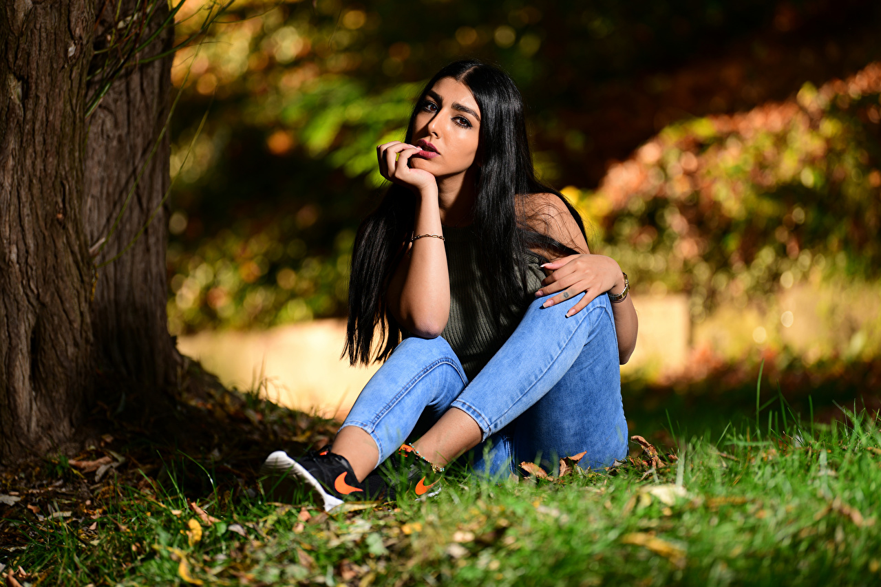 Picture Brunette girl blurred background Girls Jeans sit Grass Staring Bokeh female young woman Sitting Glance