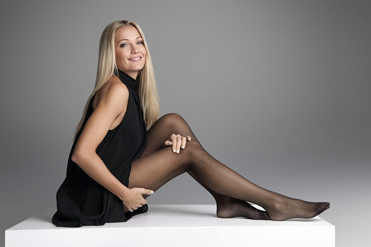 Desktop Wallpapers Pantyhose Blonde girl Modelling Smile Caroline Fleming Girls Legs Hands Sitting Gray background Dress Model female young woman sit gown frock