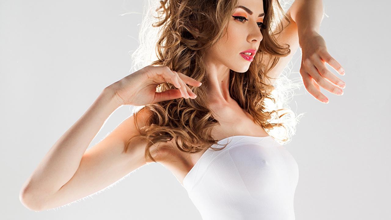 Fotos Braunhaarige locken Frisur Haar junge Frauen Hand Grauer Hintergrund Braune Haare Lockige Frisuren Mädchens junge frau