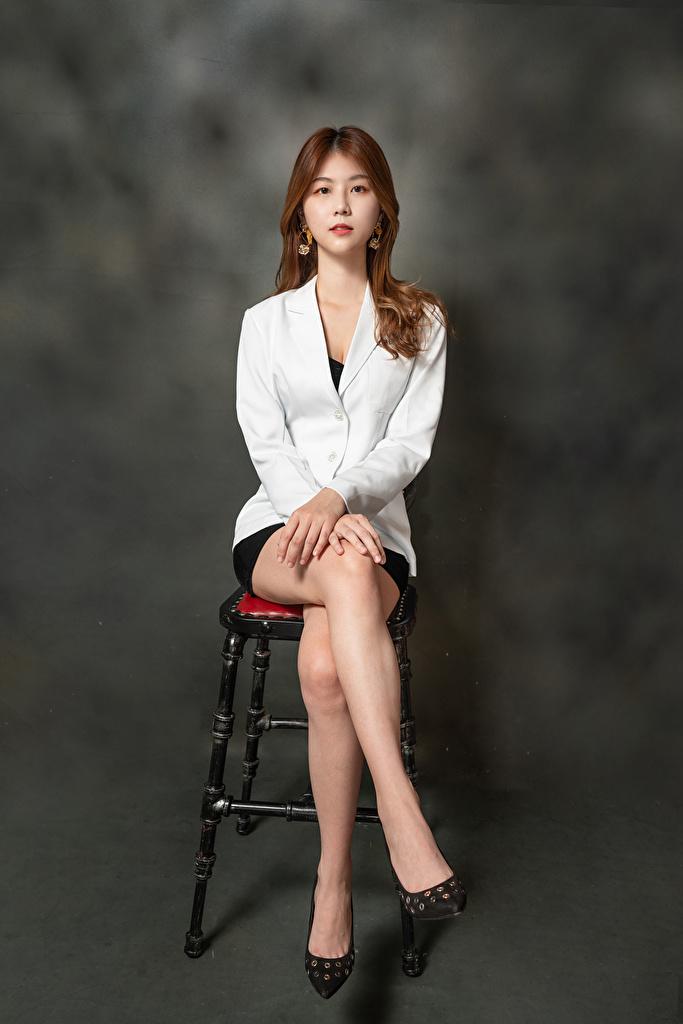 Desktop Hintergrundbilder Braunhaarige junge Frauen Bein Asiaten Stuhl sitzen Sakko Starren  für Handy Braune Haare Mädchens junge frau Asiatische asiatisches sitzt Stühle Sitzend Blick