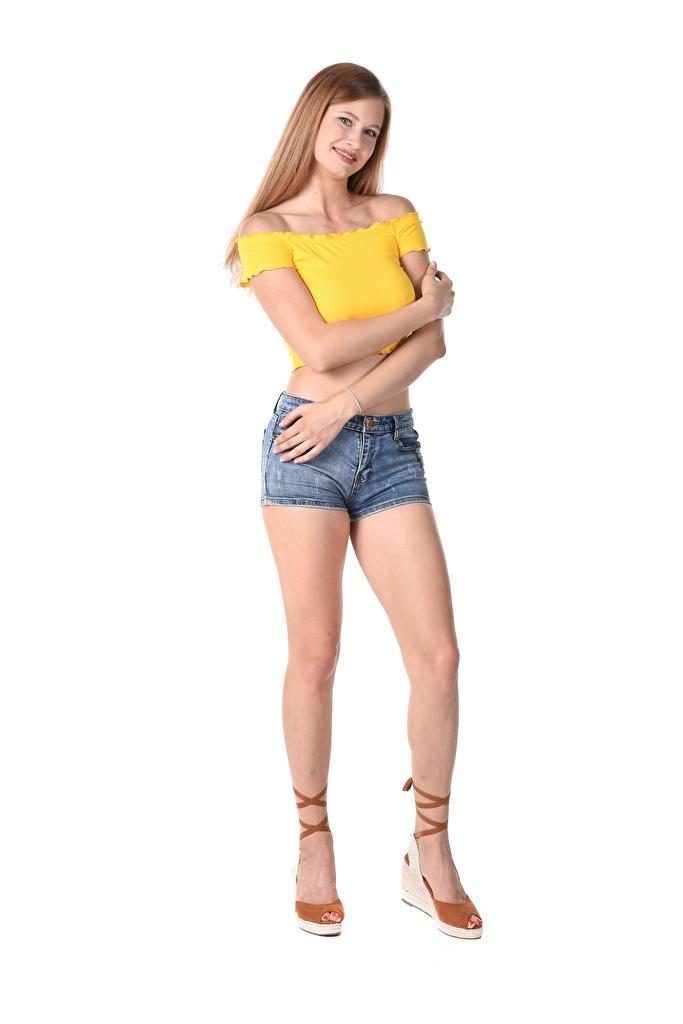 Fotos Braune Haare Lächeln Stella Cardo posiert junge Frauen Bein Hand Shorts Weißer hintergrund High Heels  für Handy Braunhaarige Pose Mädchens junge frau Stöckelschuh
