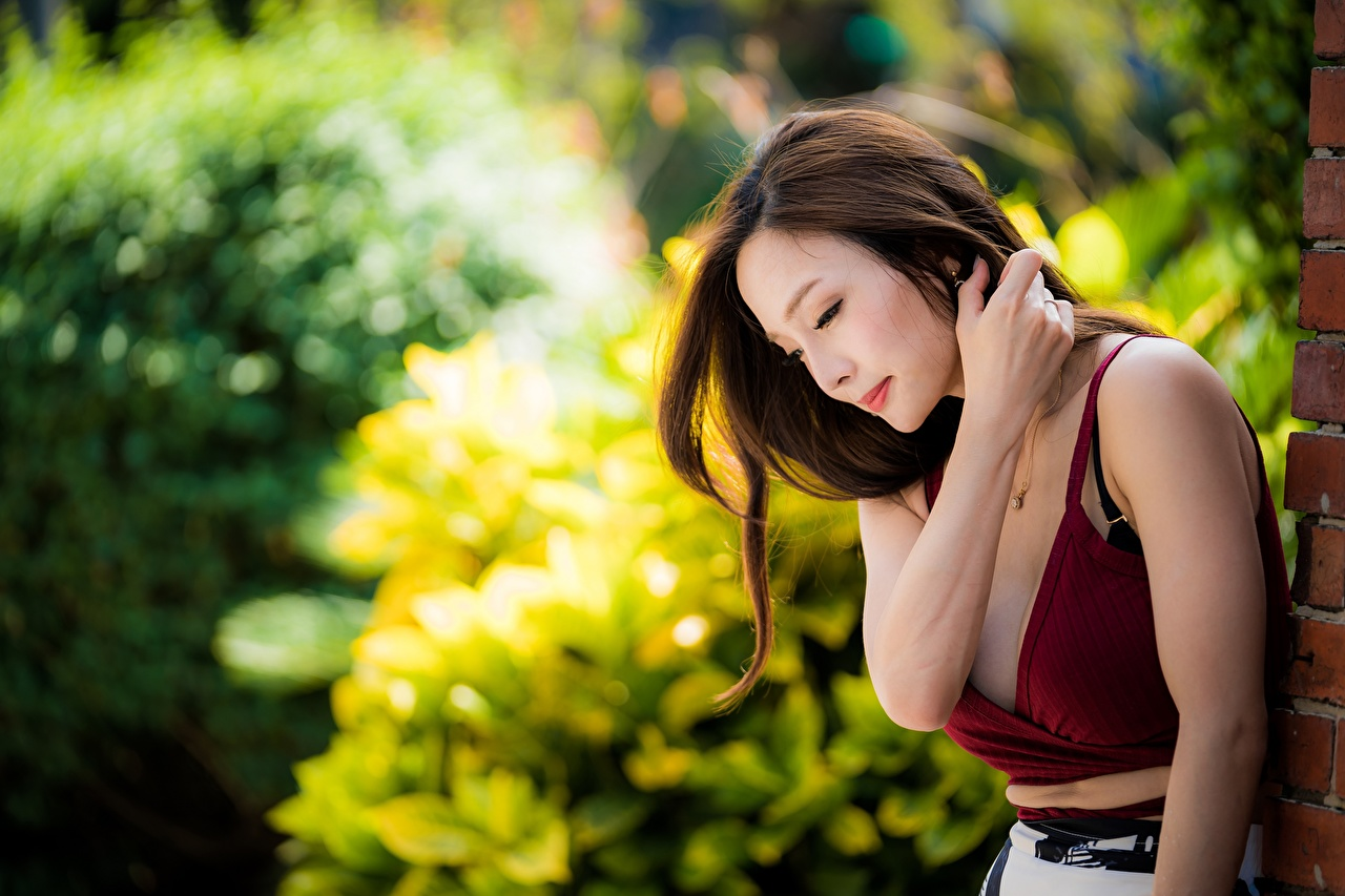Fotos Braunhaarige unscharfer Hintergrund junge Frauen asiatisches Hand Braune Haare Bokeh Mädchens junge frau Asiaten Asiatische