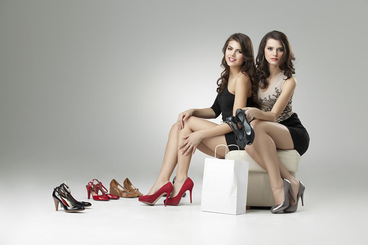 Foto Braunhaarige Lächeln 2 junge frau Bein Sitzend Handtasche Grauer Hintergrund High Heels Braune Haare Zwei Mädchens junge Frauen sitzt sitzen Stöckelschuh