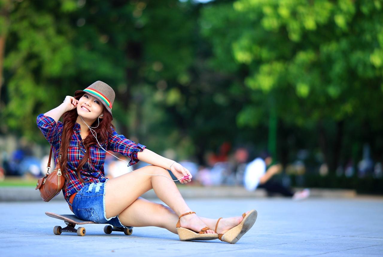 Desktop Hintergrundbilder Lächeln unscharfer Hintergrund Der Hut Mädchens Bein Asiatische Skateboard sitzt Shorts Handtasche Bokeh junge frau junge Frauen Asiaten asiatisches sitzen Sitzend