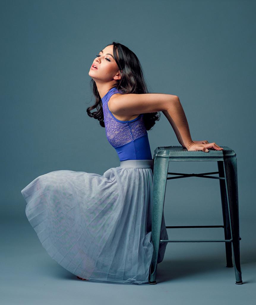 Foton Maya ung kvinna Sitter En stol Klänning Färgad bakgrund Unga kvinnor Stolar