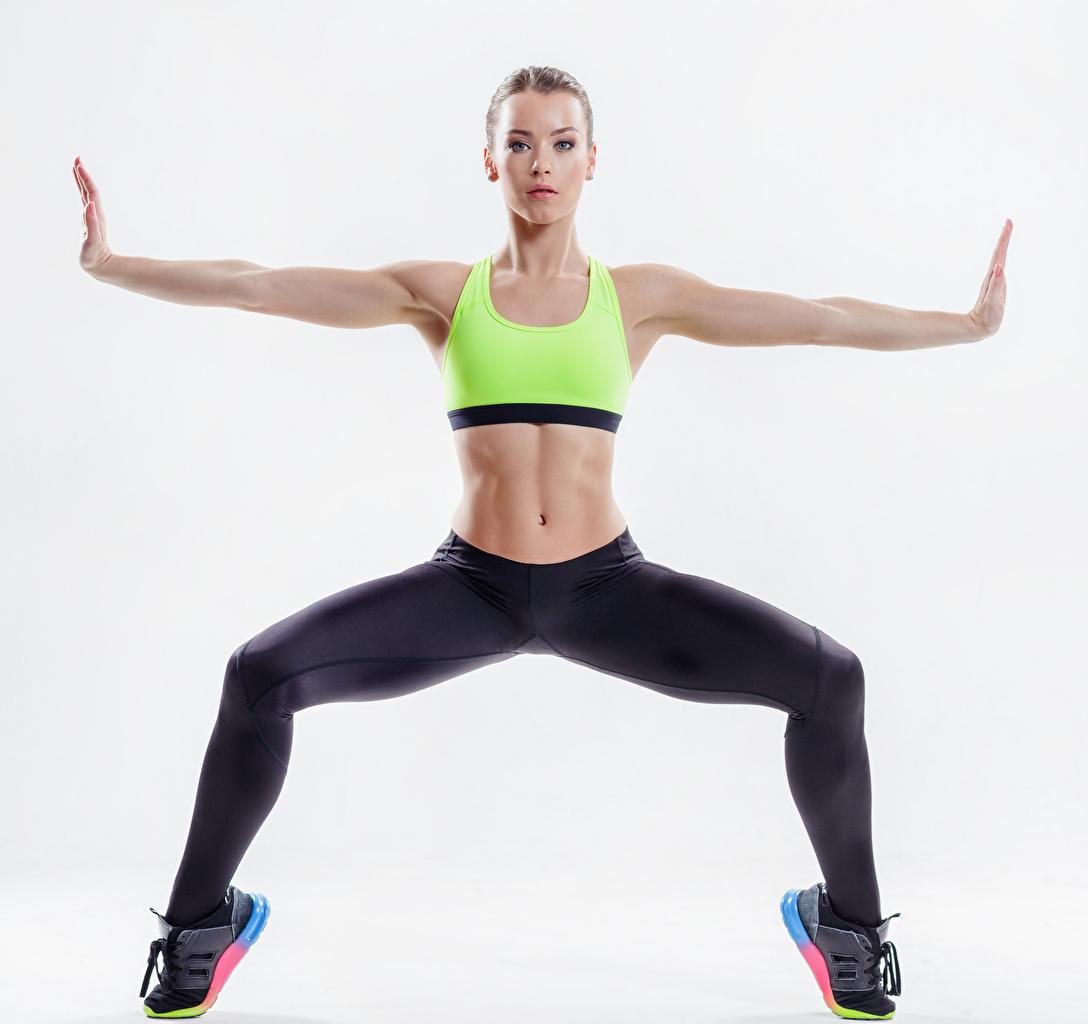 Bilder Trainieren Fitness Sport Mädchens Hand Bauch Blick Weißer hintergrund Körperliche Aktivität Starren