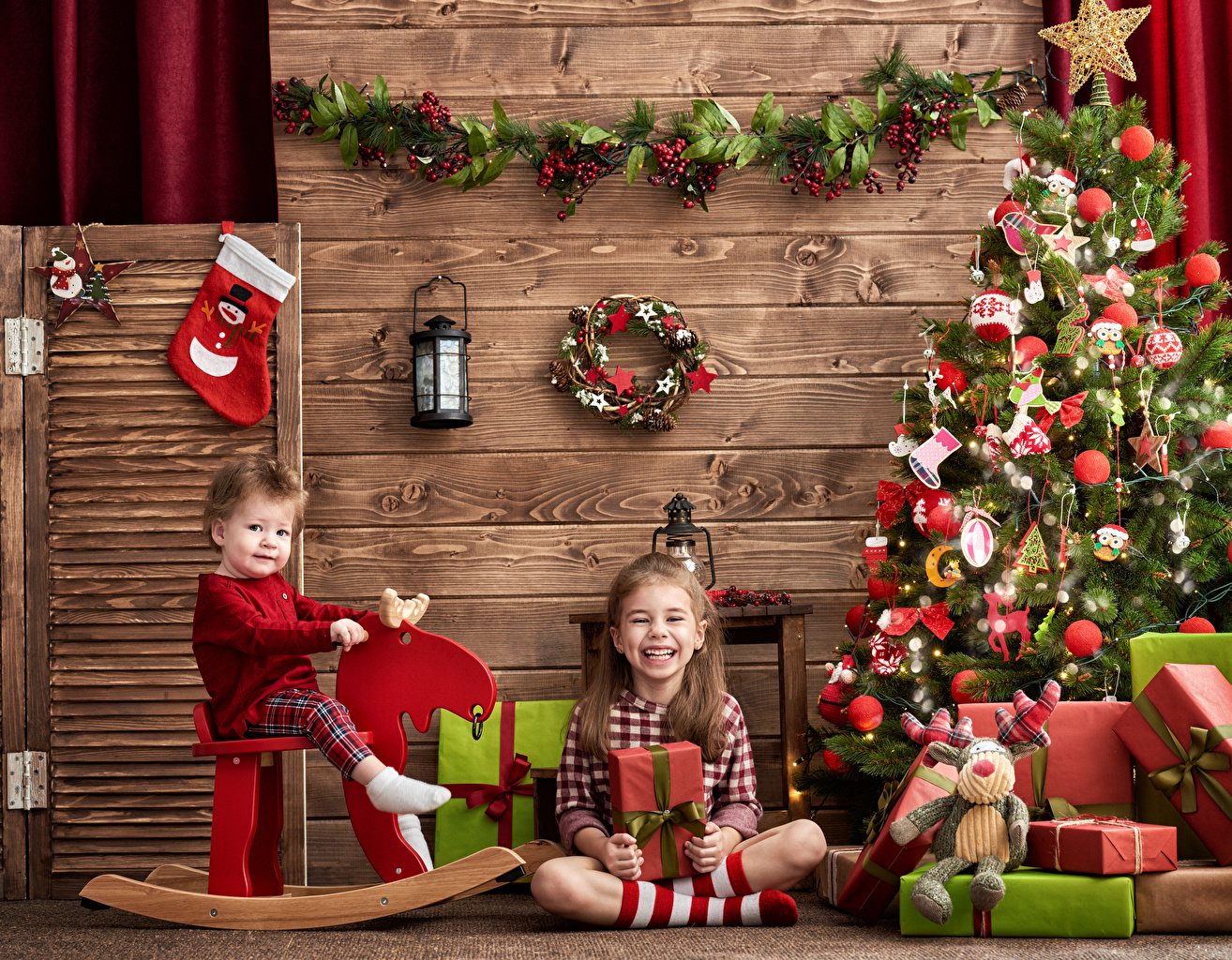 Pictures Little girls New year Lantern Smile Children Two New Year tree present Holidays Christmas child 2 Christmas tree Gifts