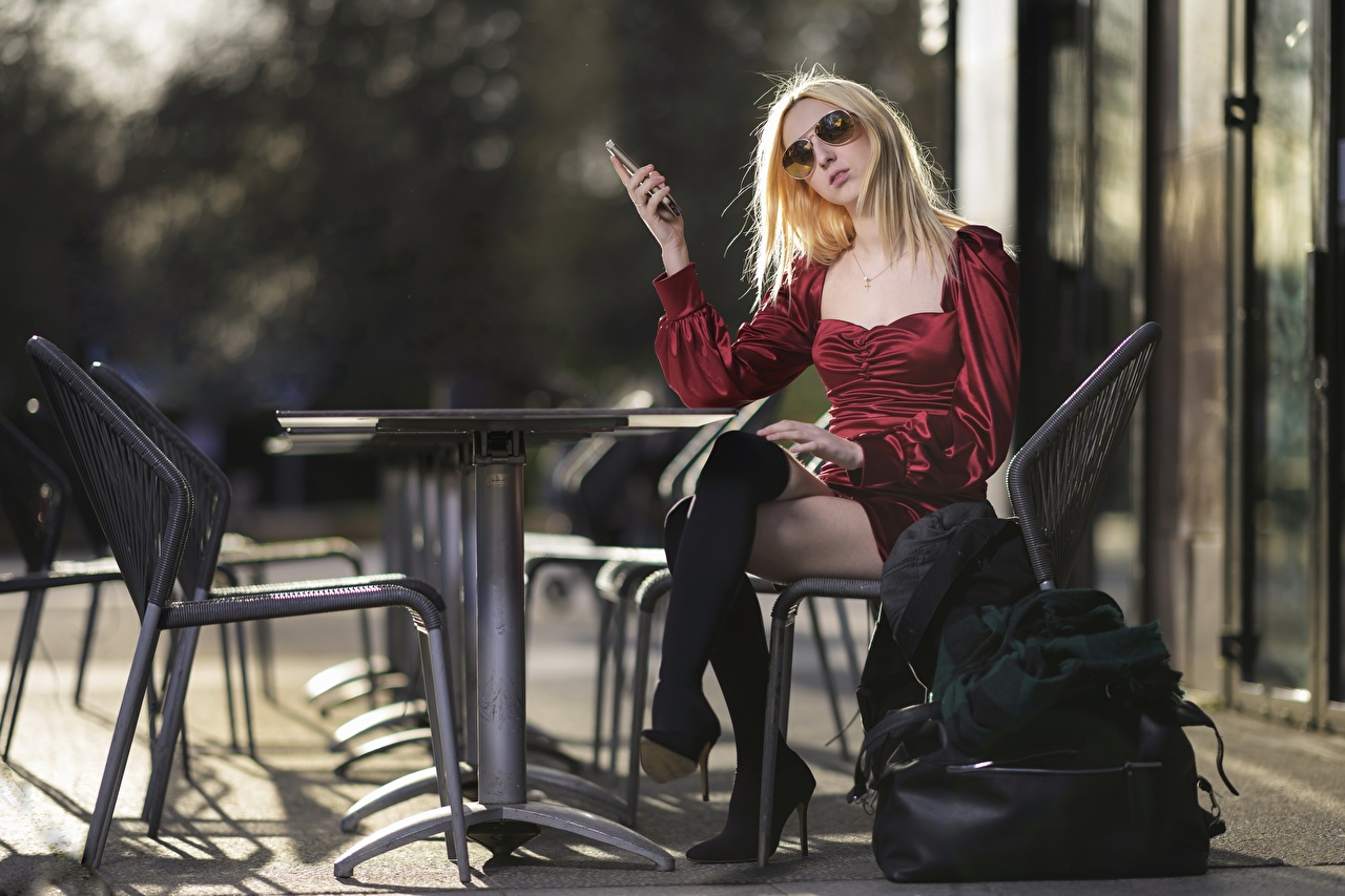 Desktop Wallpapers Blonde girl Wearing boots female Legs Table Chair Sitting Glasses Handbag gown Girls young woman sit purse Chairs eyeglasses Dress frock