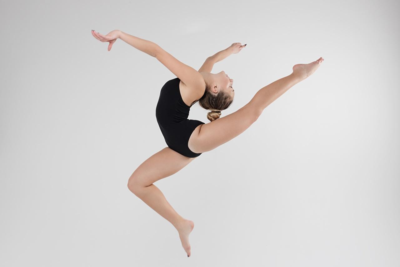 Fotos von Trainieren Schön Sport Mädchens Gymnastik Bein Sprung Hand Grauer Hintergrund Körperliche Aktivität hübsch schöne hübsche schöner schönes hübscher junge frau sportliches junge Frauen