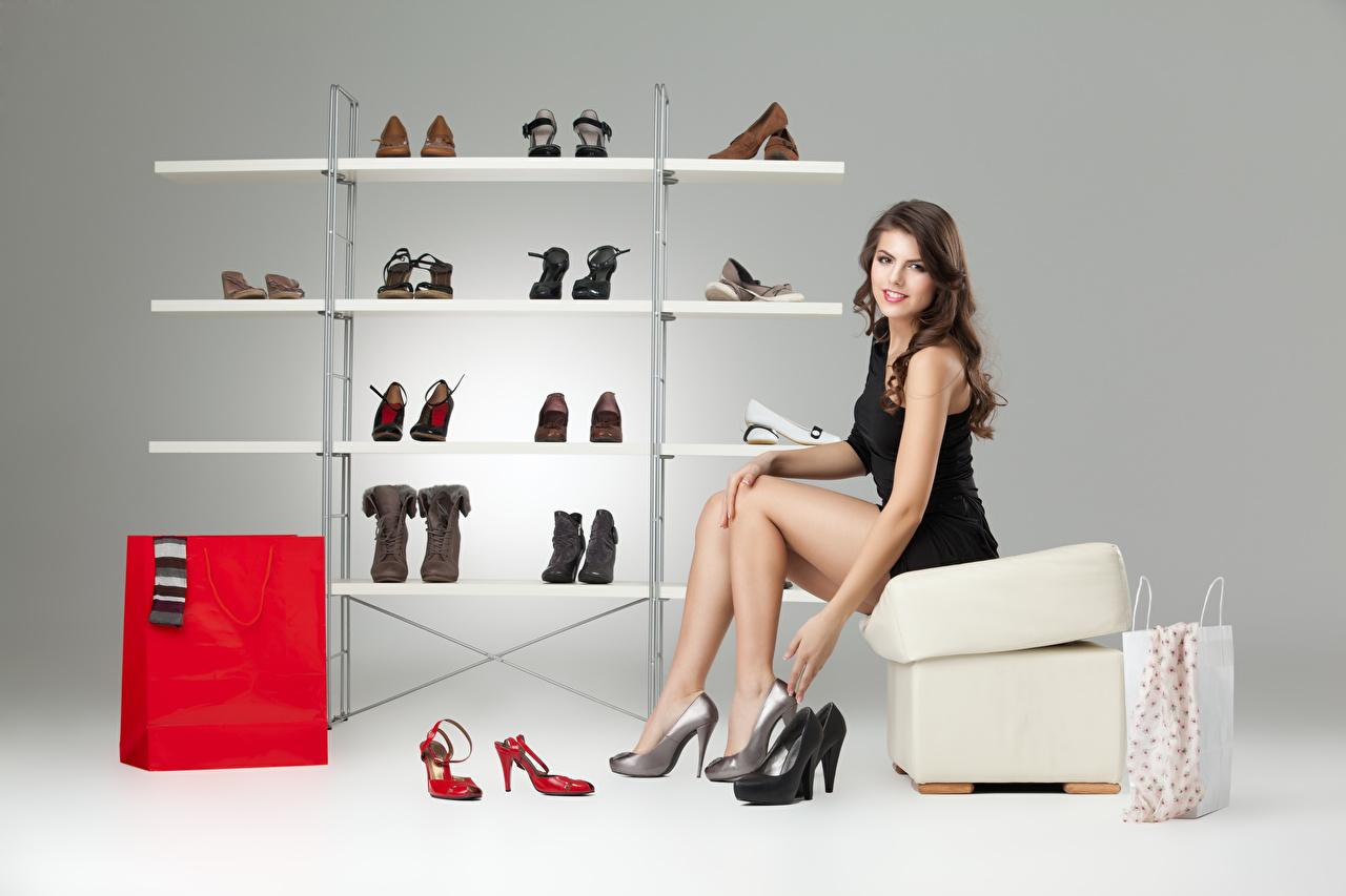 Bilder Braunhaarige Model Mädchens Bein Hand Sitzend Grauer Hintergrund Kleid Stöckelschuh Braune Haare junge frau junge Frauen sitzt sitzen High Heels