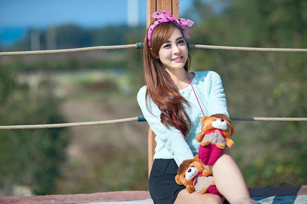 Bilder Lächeln Bokeh Mädchens asiatisches Sitzend Schleife Blick Spielzeuge unscharfer Hintergrund junge frau junge Frauen Asiaten Asiatische sitzt sitzen Starren Spielzeug