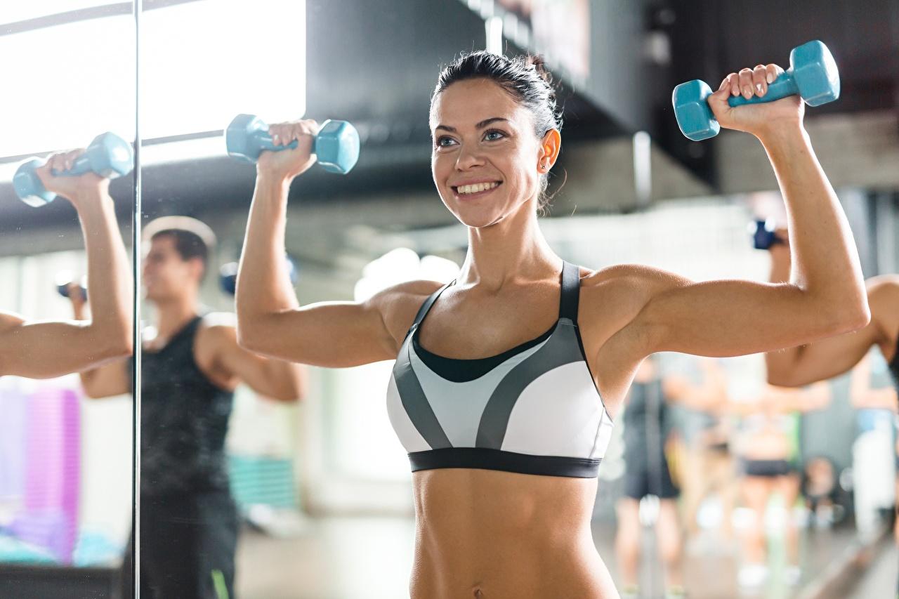 Fotos von Muskeln Turnhalle Körperliche Aktivität Lächeln Fitness Sport Hantel junge frau Hand Trainieren Fitnessstudio Hanteln Mädchens sportliches junge Frauen