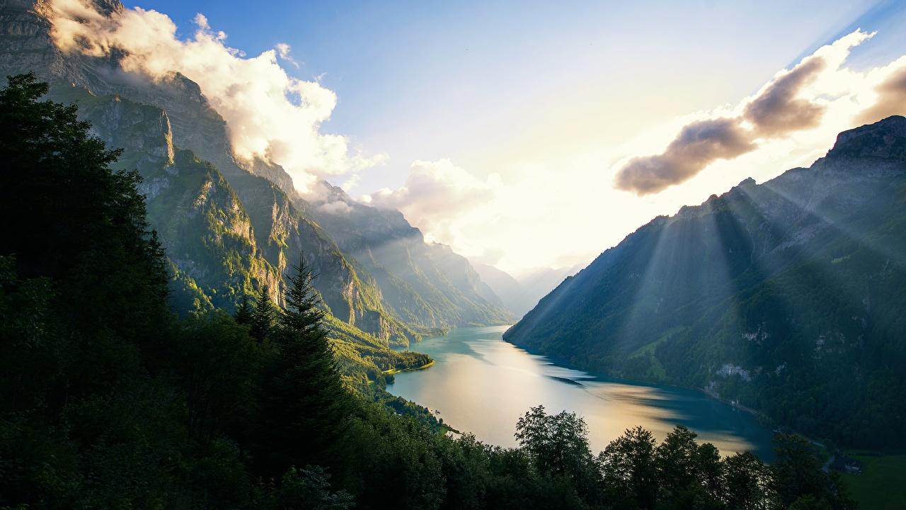 Desktop Wallpapers Rays of light Alps Switzerland Klontalersee Nature Mountains Lake mountain
