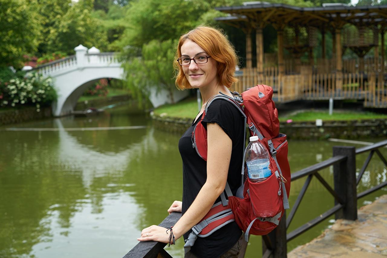 Fotos Reisender Rotschopf Lächeln Rucksack unscharfer Hintergrund Mädchens Parks Brille Starren Tourist Bokeh junge frau junge Frauen Park Blick