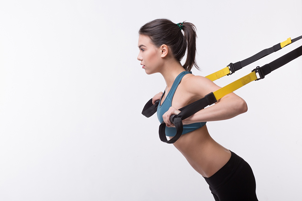 Bilder Brünette Körperliche Aktivität Fitness junge frau sportliches Grauer Hintergrund Trainieren Sport Mädchens junge Frauen