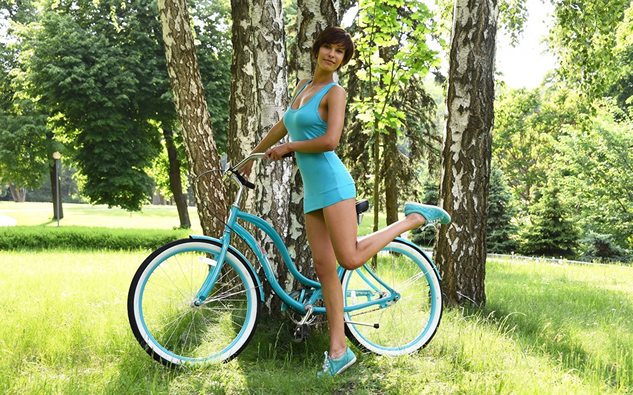 Pictures Brunette girl posing bike Birch female Legs Grass Hands gown Pose Bicycle bicycles Girls young woman frock Dress