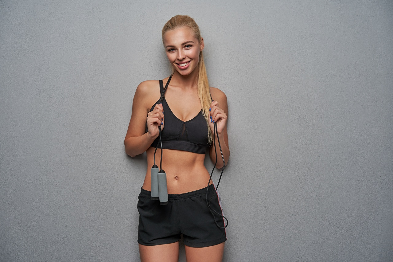 Picture Blonde girl Smile Fitness Girls athletic Staring Gray background Sport female sports young woman Glance