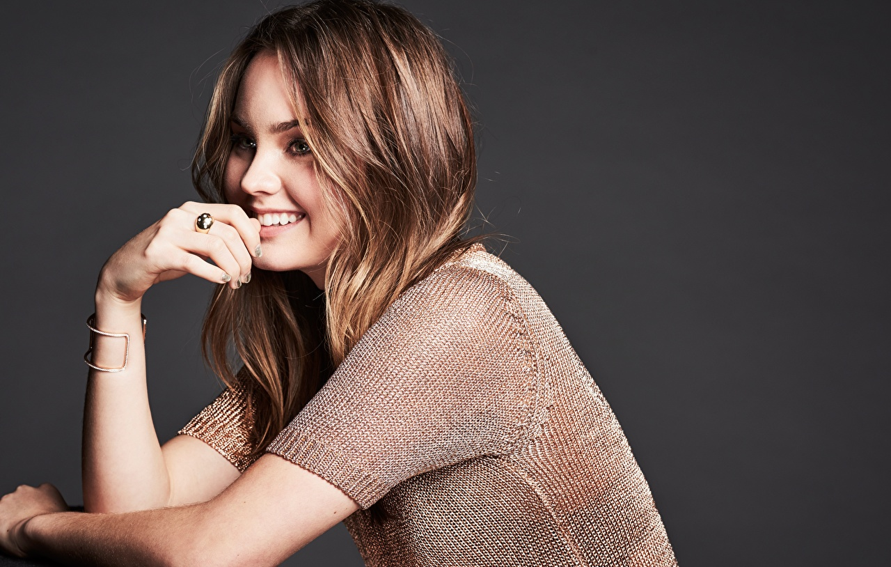 Photos Brown haired Smile Liana Liberato female jewelry ring Hands Staring Celebrities Gray background Girls young woman Ring Glance
