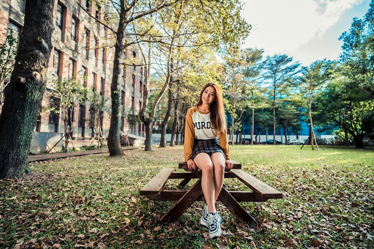 Fotos von Braune Haare Lächeln junge Frauen Bein Asiatische Tisch sitzen Starren Braunhaarige Mädchens junge frau Asiaten asiatisches sitzt Sitzend Blick