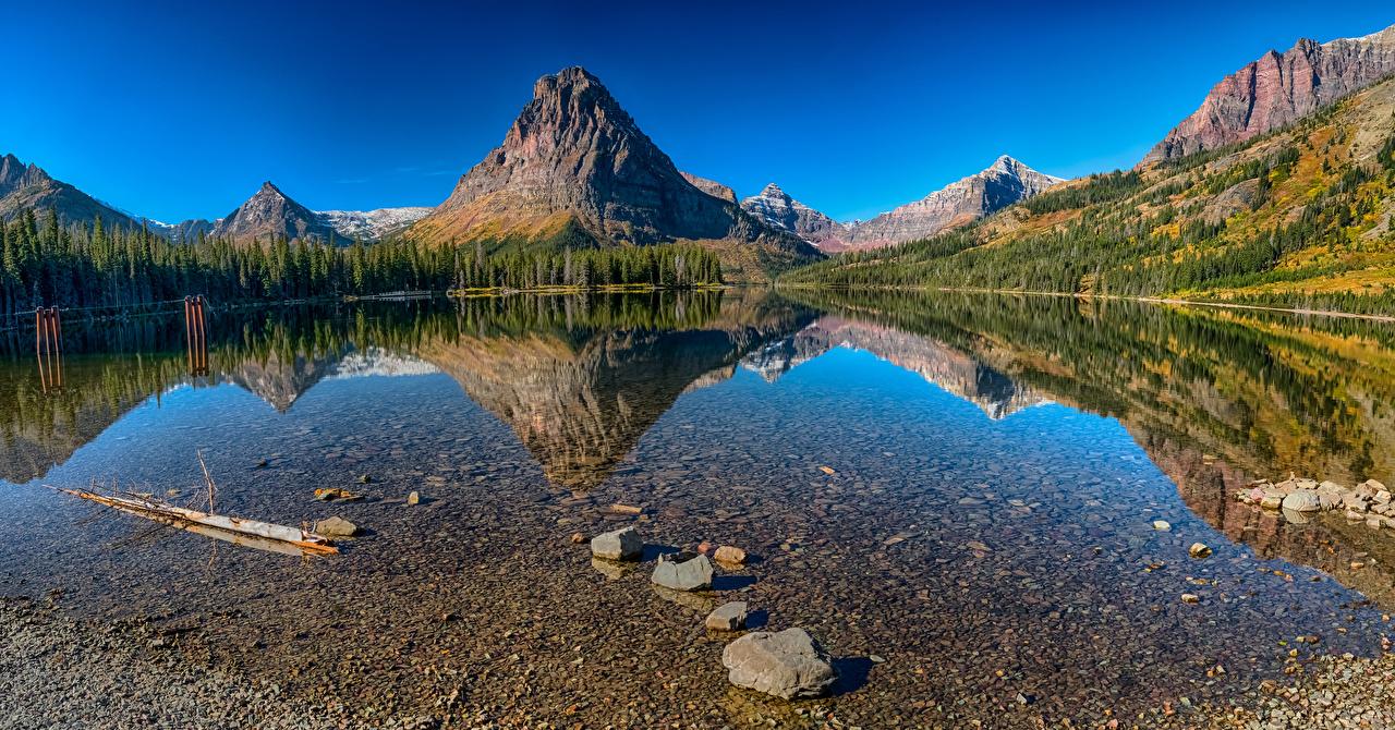 Fotos USA Medecine Lake Glacier National Park Natur Gebirge See Wald Parks Reflexion Landschaftsfotografie Stein Vereinigte Staaten Berg Wälder spiegelt Spiegelung Spiegelbild Steine