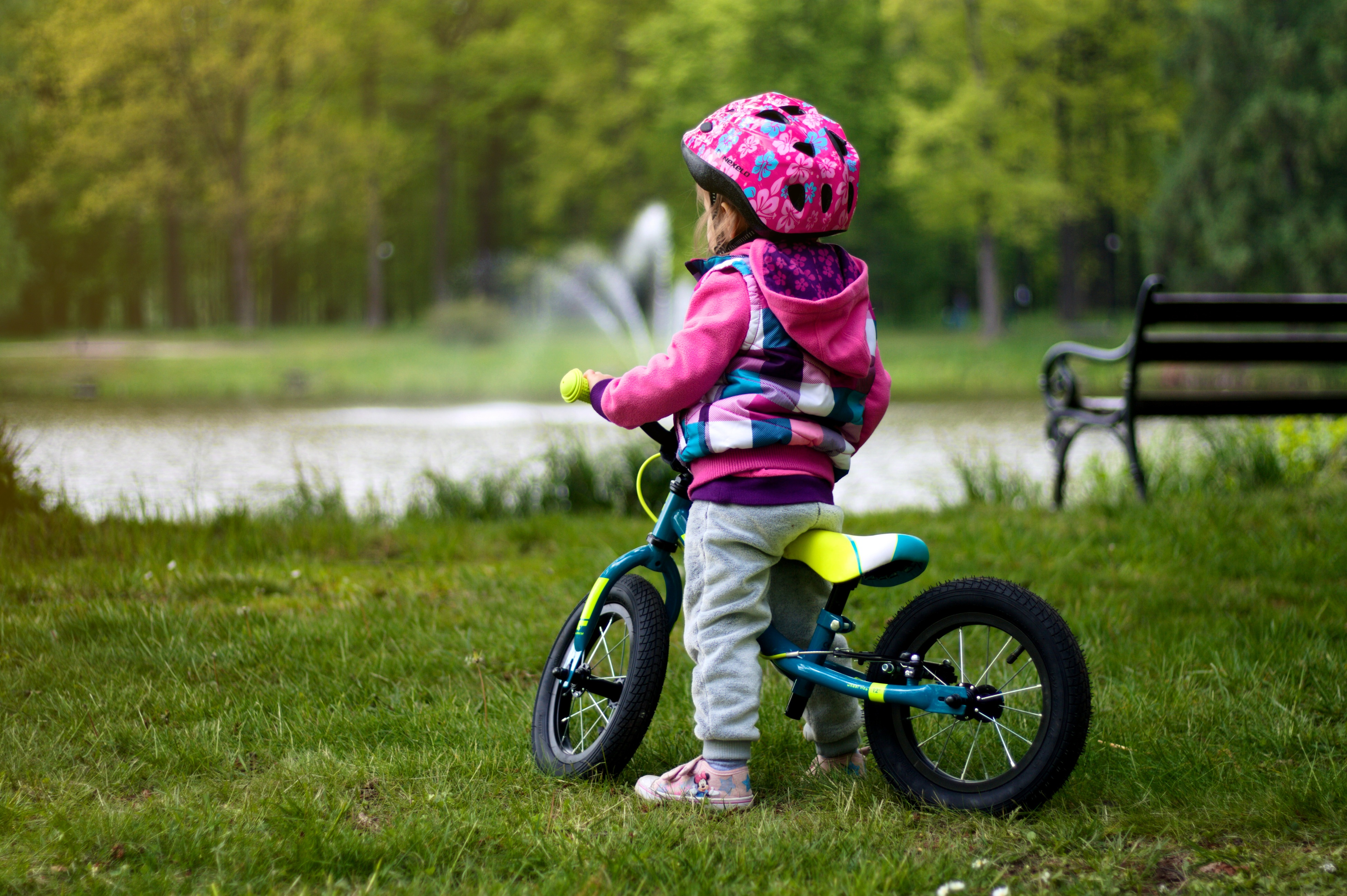 Bilder Kleine Mädchen Helm kind fahrräder Gras Kinder Fahrrad