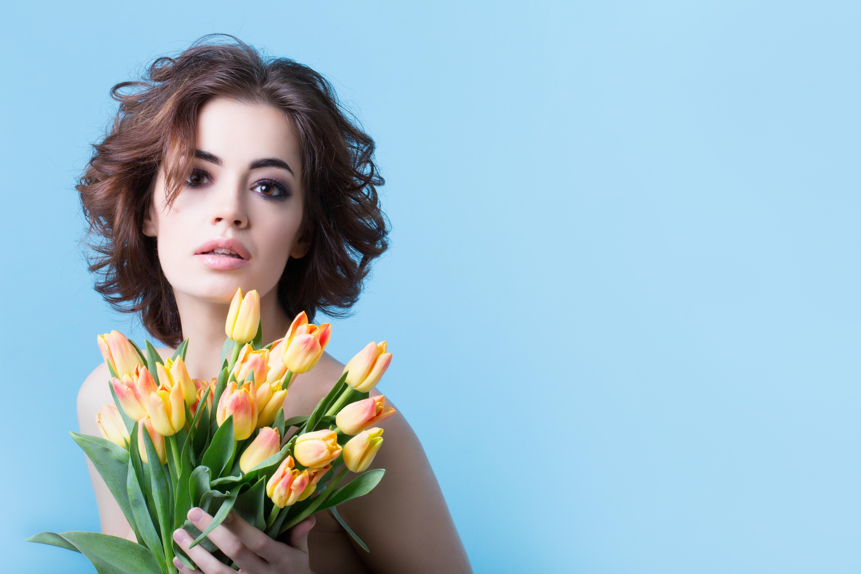 Fotos von Braunhaarige Model Sträuße Tulpen Mädchens Blüte Starren Farbigen hintergrund Braune Haare Blumensträuße junge frau junge Frauen Blumen Blick