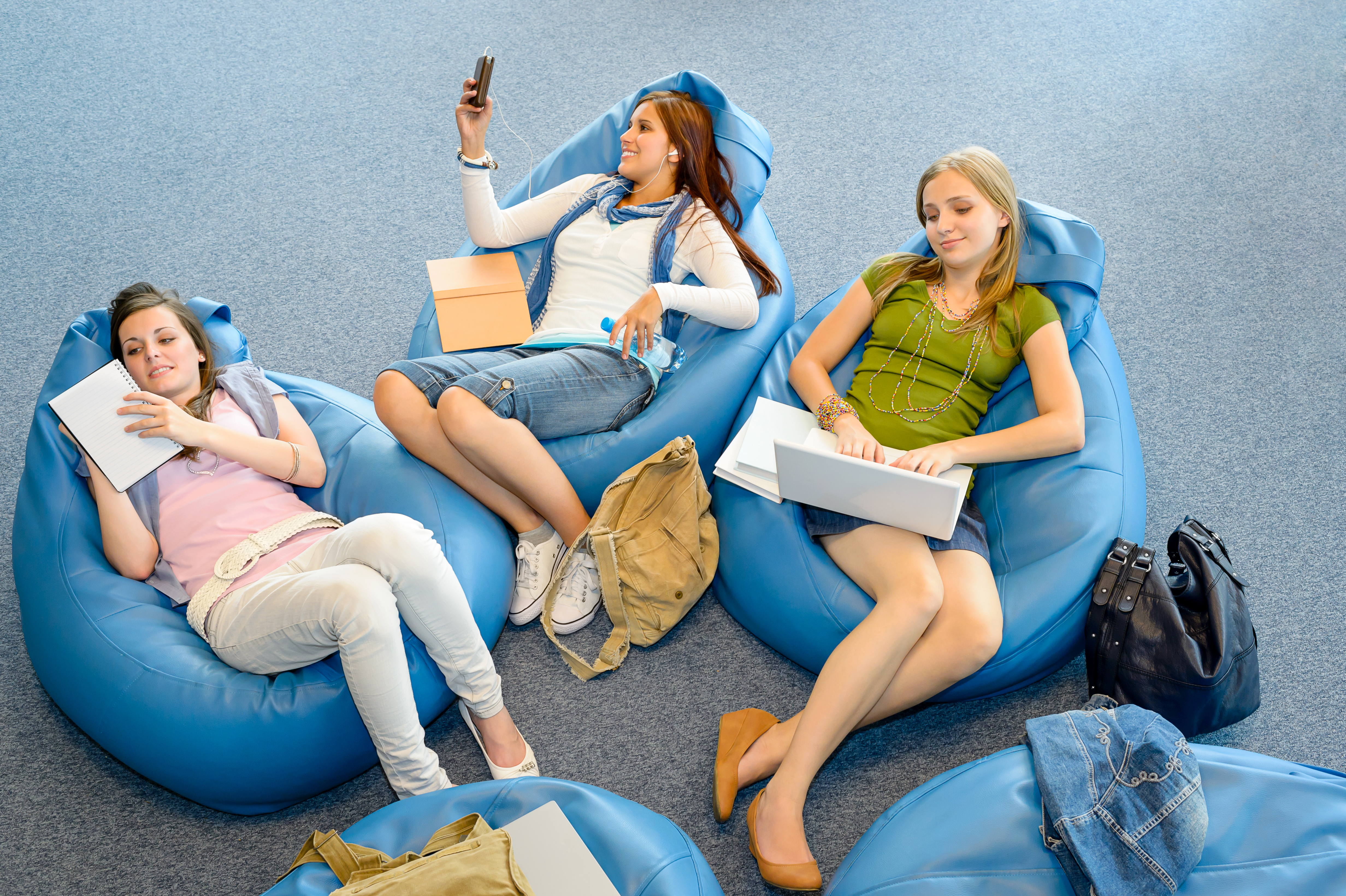 Bilder von Notebook Lächeln smartphones junge Frauen sitzt Drei 3 Handtasche Smartphone Mädchens junge frau sitzen Sitzend