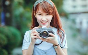 Bilder Asiatische Fotoapparat Braune Haare Lächeln Fotograf junge Frauen