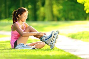 Bilder Kleine Mädchen Braune Haare Lächeln Gras Unterhemd Sitzend Rollschuh Kinder