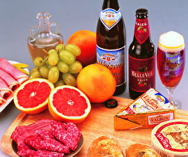 Pictures Still-life Beer Sausage Citrus Grapes Grapefruit Bottles Stemware Food