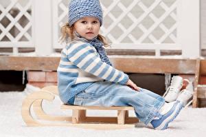 Fotos Kleine Mädchen Starren Jeans Sweatshirt Sitzen Mütze Schlitten Kinder