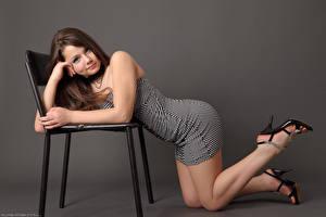 Bilder Kleofia model Farbigen hintergrund Braunhaarige Kleid Stühle Bein High Heels Model Posiert junge frau