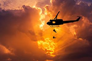Pictures Helicopter Sunrises and sunsets Landing operation Silhouette Rays of light Clouds American Bell UH-1 Iroquois Aviation Army