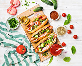 Fotos Fast food Hotdog Gemüse Tomate Gurke Gewürze Schneidebrett