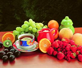 Fotos Stillleben Tee Weintraube Erdbeeren Himbeeren Apfelsine Tasse