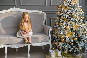 Bilder Feiertage Neujahr Sofa Kleine Mädchen Tannenbaum Kugeln Sitzend Geschenke kind
