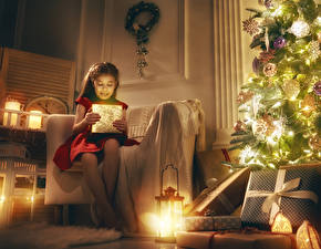 Fotos Neujahr Feiertage Kleine Mädchen Tannenbaum Laterne Geschenke Sessel Sitzt kind